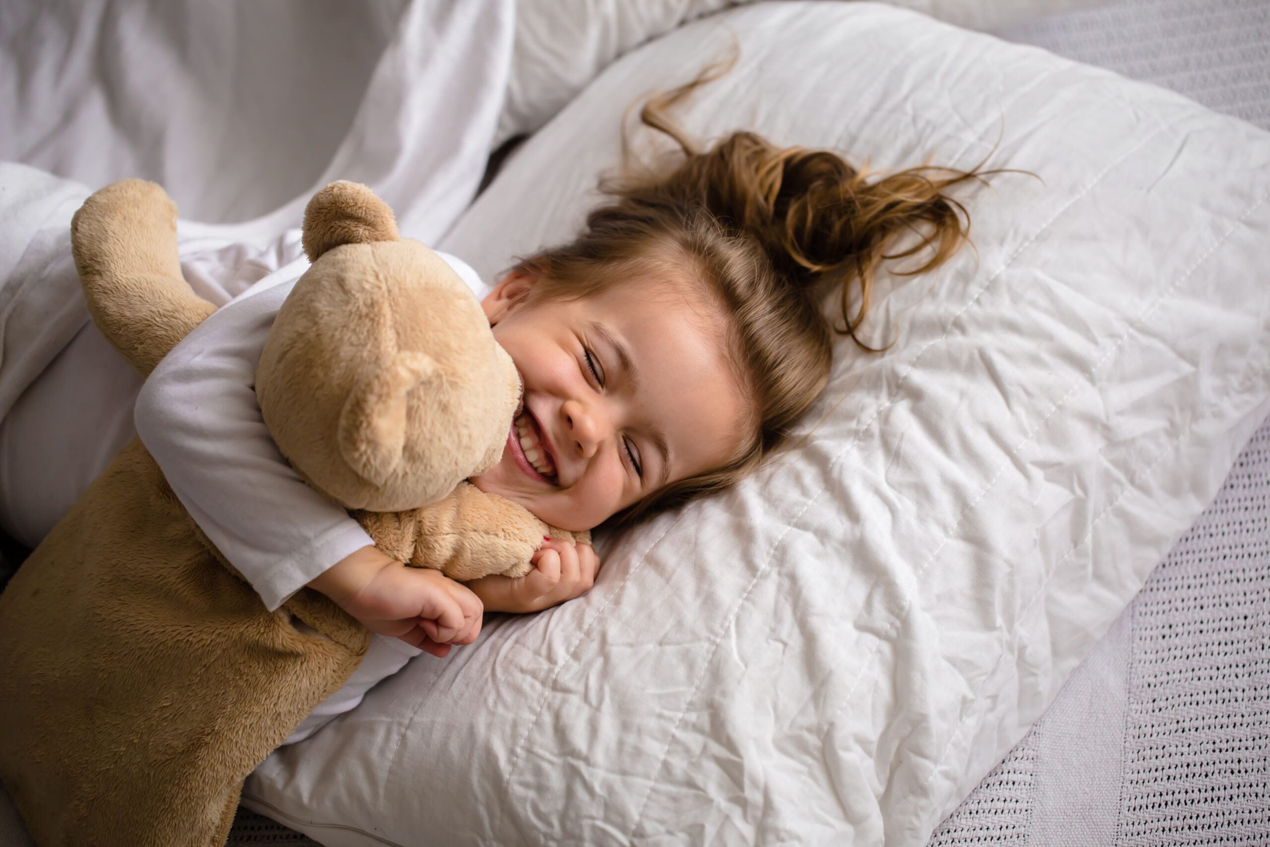 little girl in bed with soft toy the emotions of a child, white bed