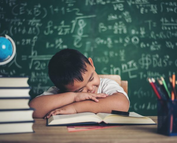 Boy sleeping on the books in the classroom.