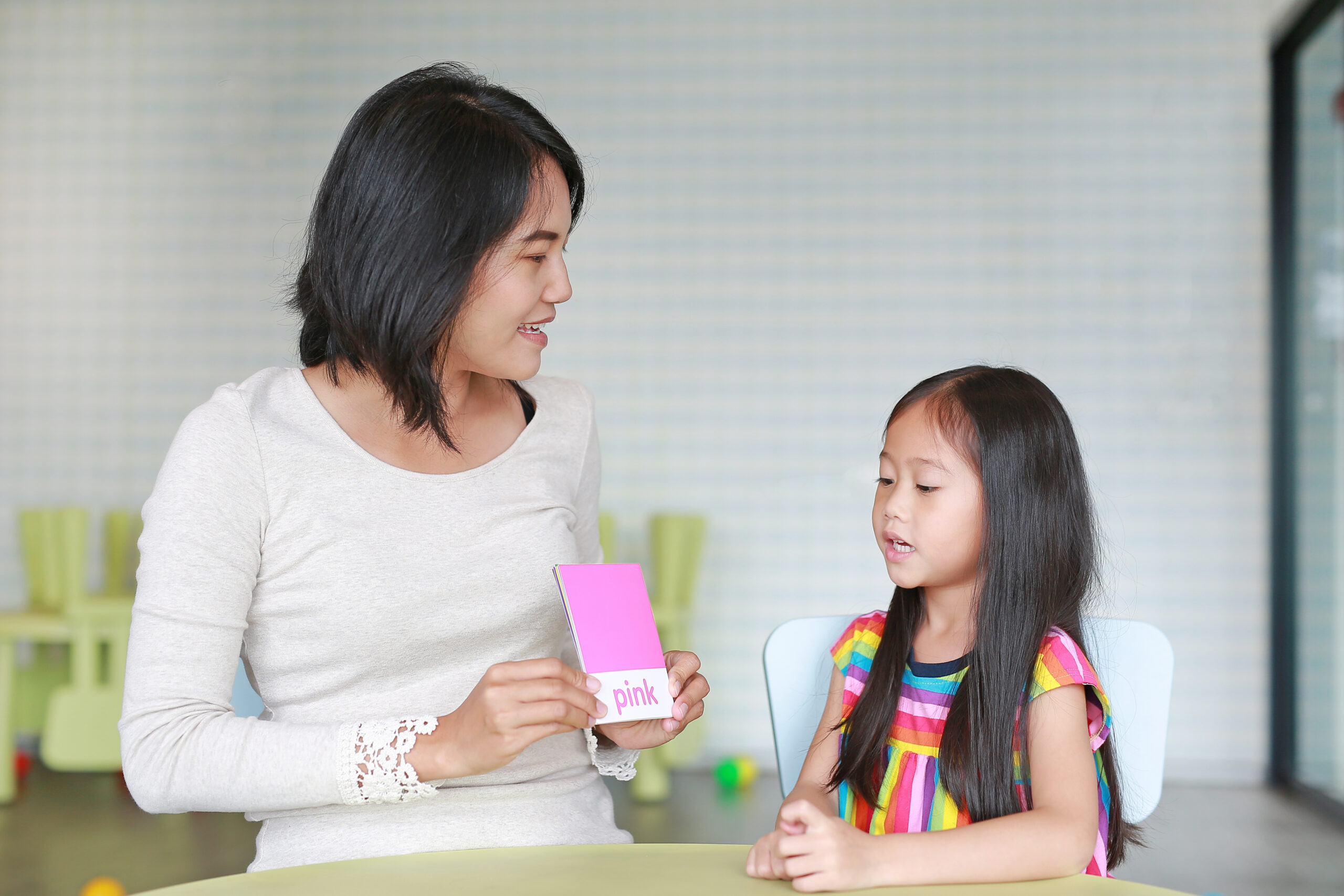 Asian mother and child girl playing flash card for Right Brain Development at the playroom. Kid learning concept.