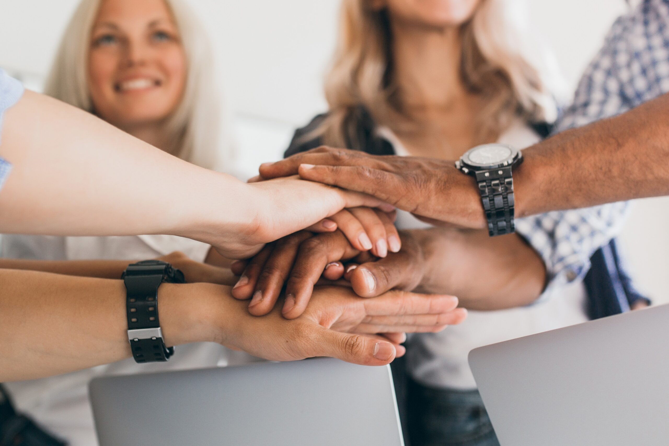 blonde-female-office-worker-looking-up-with-smile-while-holding-hands-with-colleagues-indoor-portrait-friends-ready-start-joint-work-project – Edited
